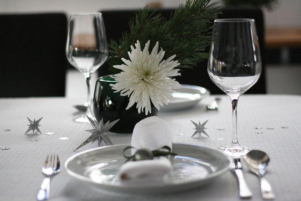 Weihnachtliche Tischdekoration in weiß und grün mit kleinen Christbaumkugeln und silbernen Sternen