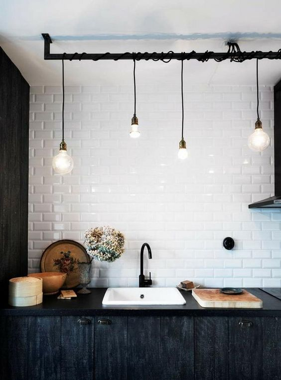 Black kitchen with exposed wire lamps
