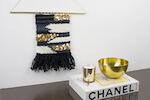 Wandteppich neben einem Coffeetable-Book Gucci auf einer Kommode. Der Wandbehang ist selbstgewebt in den Farben gold und schwarz mit dem Webrahmenset von lindaloves.de - DIY Blog aus Berlin